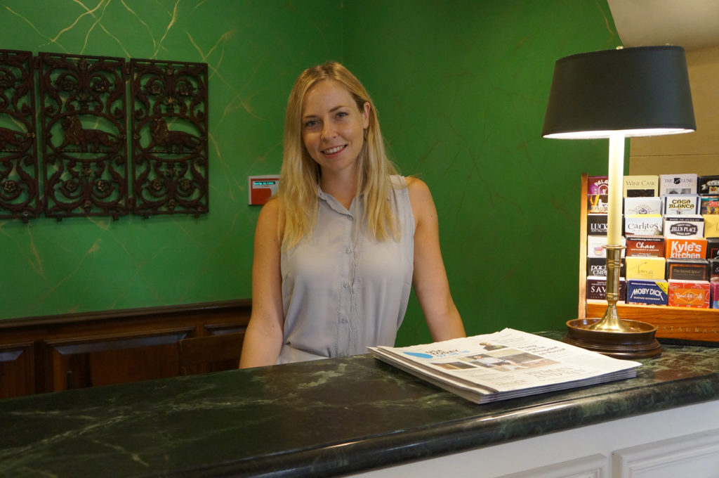 Hotel Santa Barbara staff standing behind the front desk smiling warmly