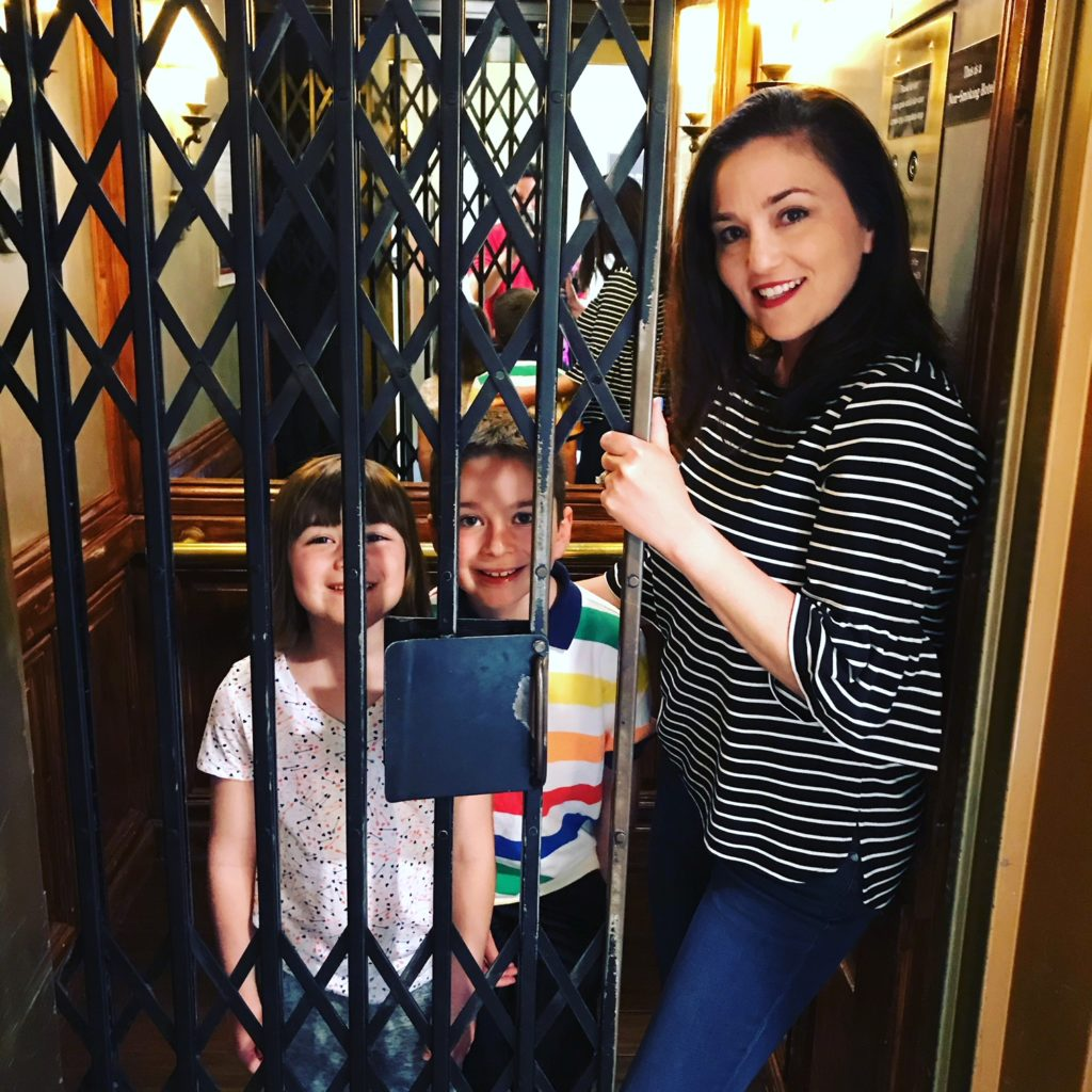 Writer Cortney Fries with her children in the antique elevator at Hotel Santa Barbara