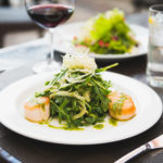 Seared scallops and a greens piled on a white plate, with a glass of wine.