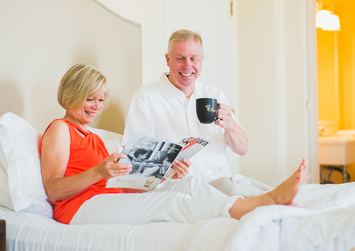 Couple drinking coffee on bed.