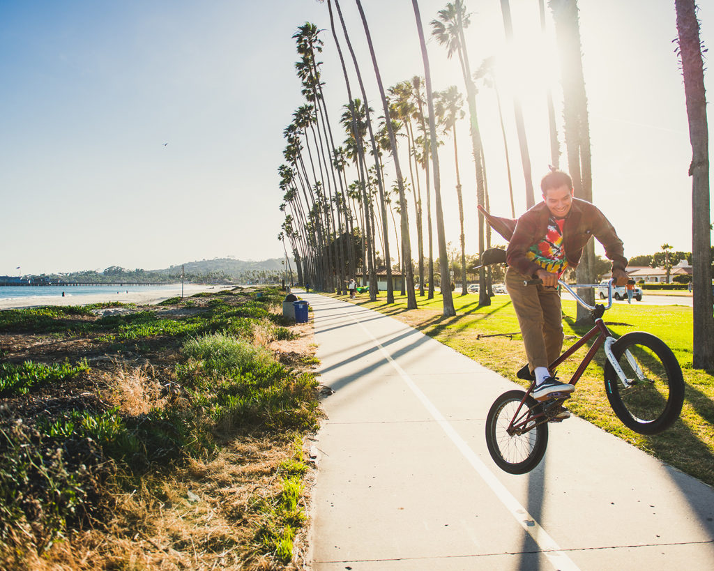 A cyclist jumping in the air on a waterfront bike path in Santa Barbara