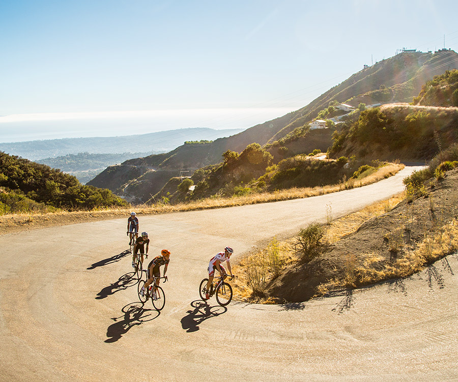 Four cyclists ride up a steap section of Gibraltar road in Santa Barbara