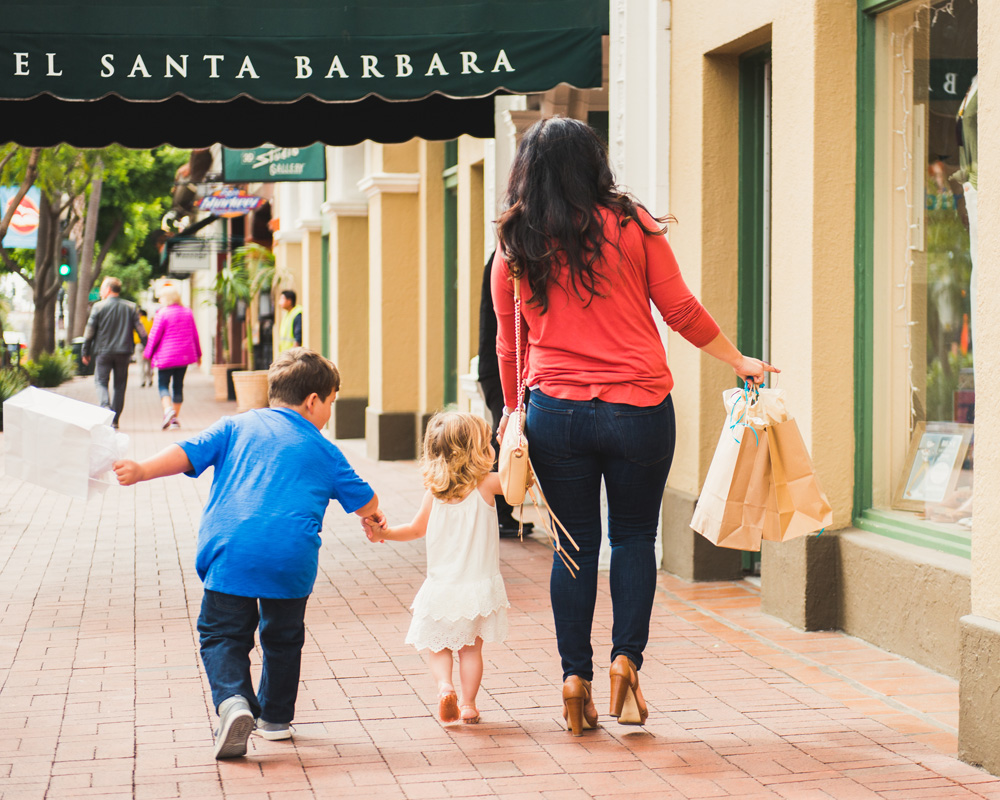 a mom and her son and daughter walking on the sidewalk with shopping bags in hand
