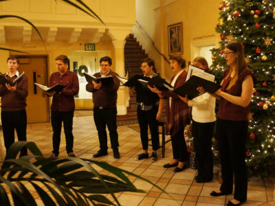 Members of Adelfo Ensemble standing in a semi circle around christmas tree singing carols