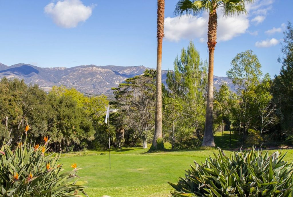 Green golf course with palm trees and views of the Santa Barbara mountains.