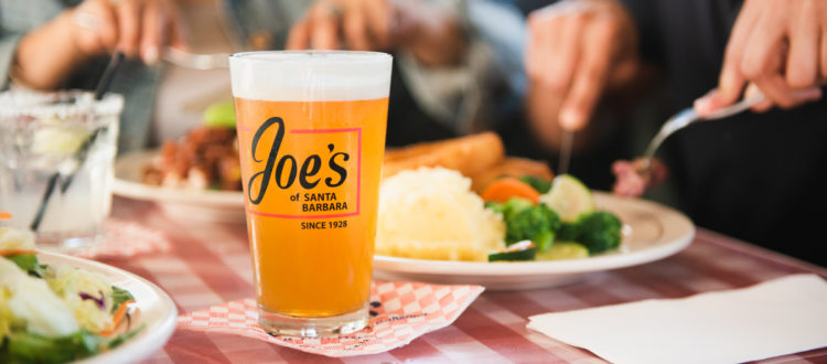 Glass of beer and plates of foot on red checked table cloth at Joe's Cafe