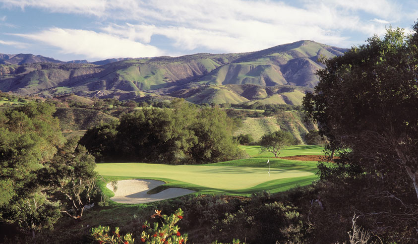 Green golf course with a backdrop of mountains and blue sky with clouds.