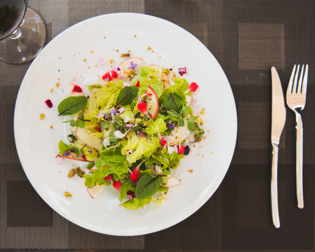 Plate of salad next to fork and knife