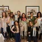 Women attending an art workshop posing for a picture and holding dream catchers