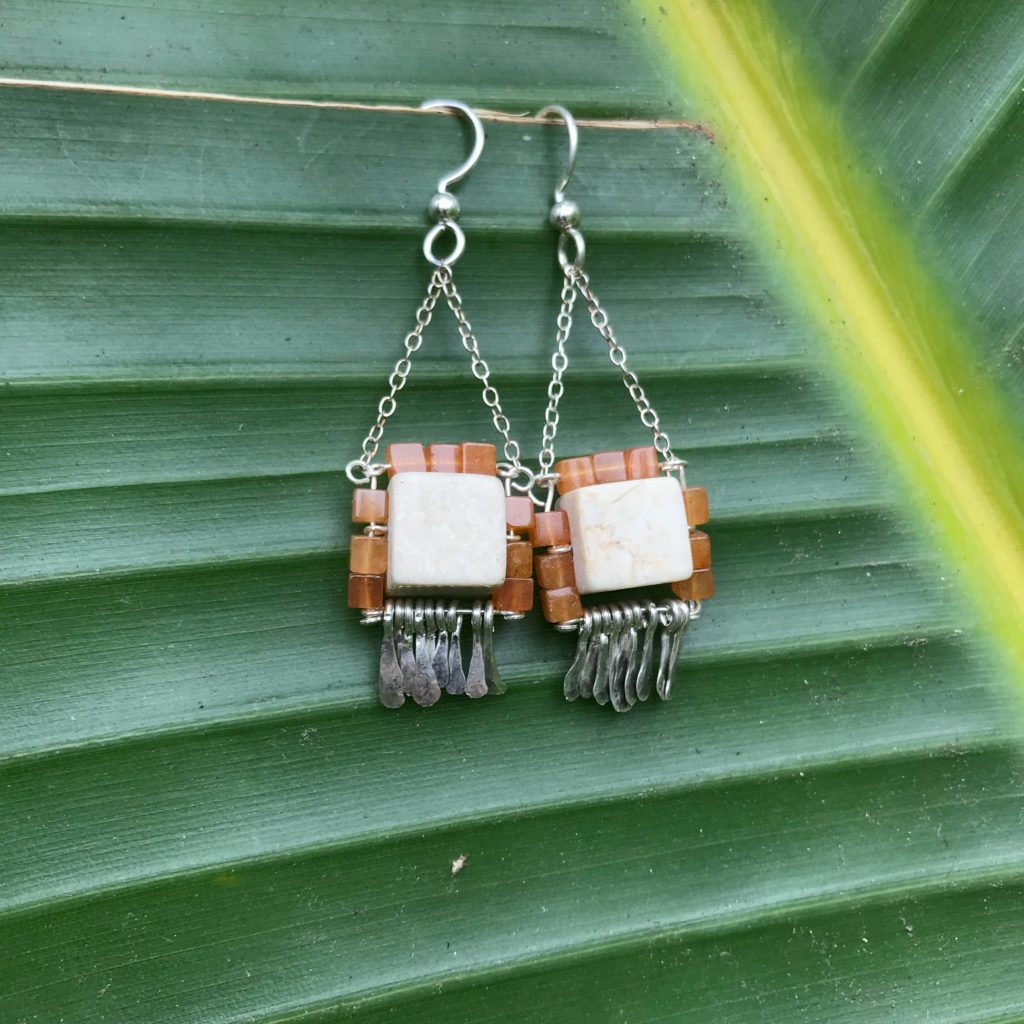 a pair of beaded dangling earrings displayed on a palm frond