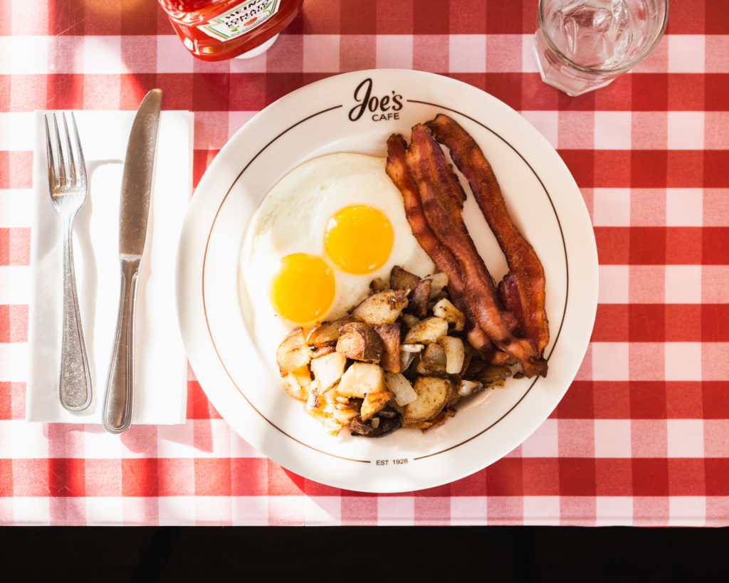 two eggs sunny-side-up, potatoes, and bacon on a plate set up on a table