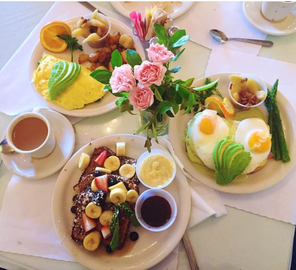 brunch plates, vase of flowers, and coffee set up on linen cloth table