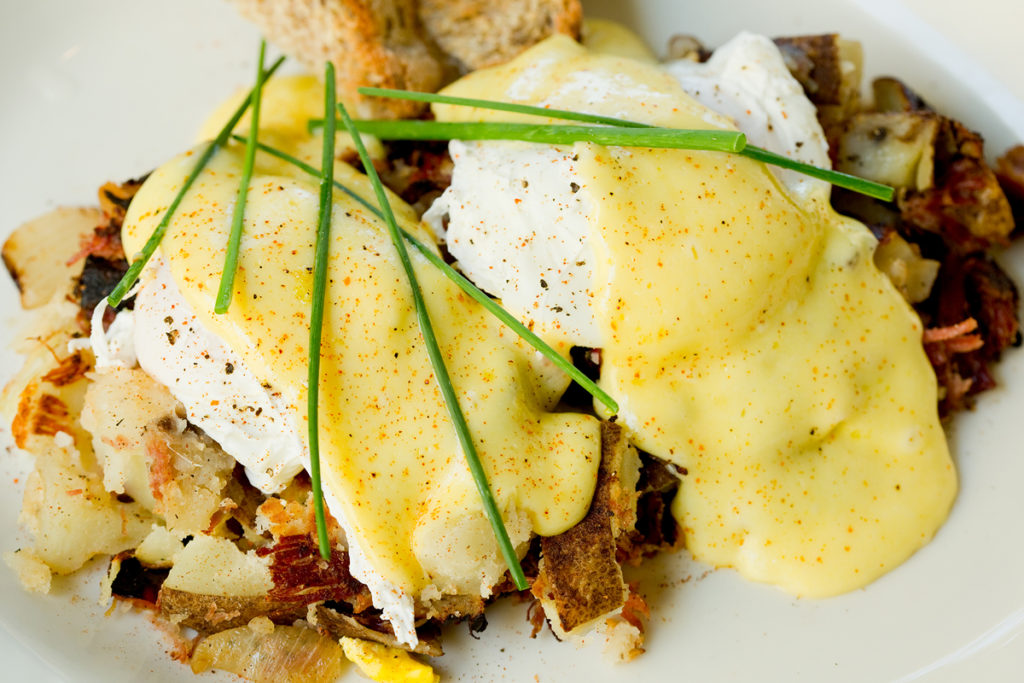 breakfast hash with fried eggs, potatoes, and hollandaise sauce