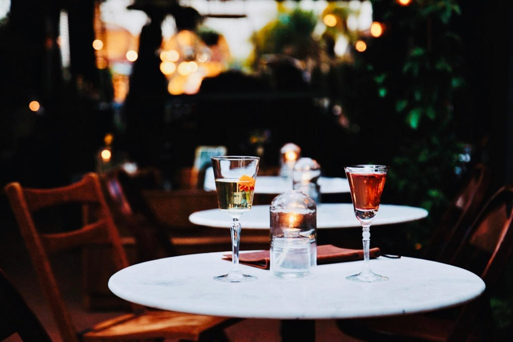 two cocktails on a round table on an outdoor patio