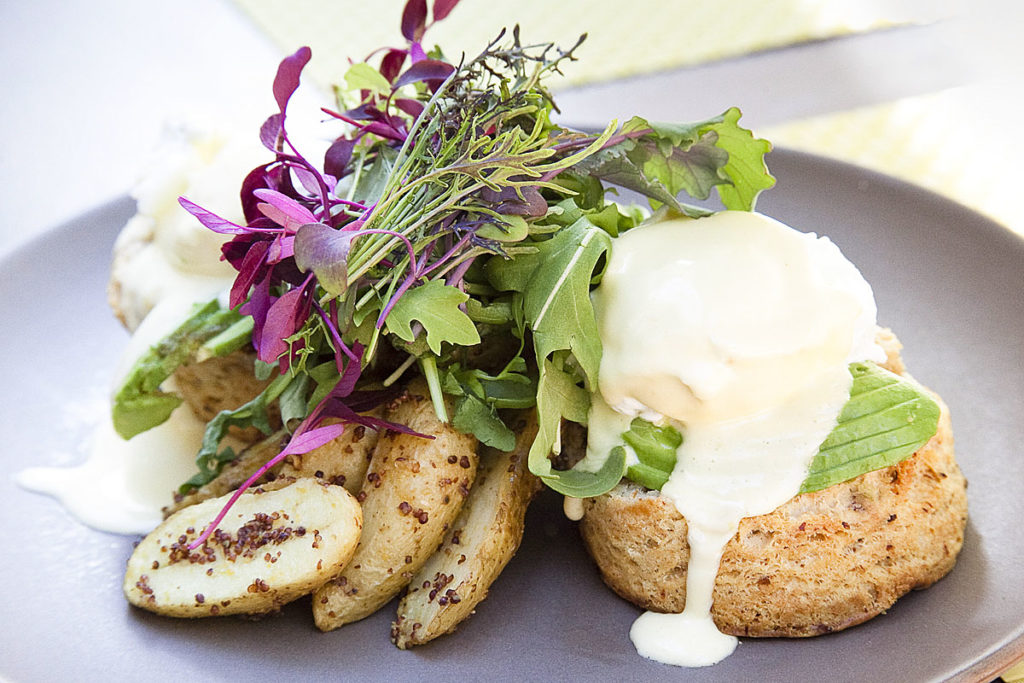 eggs benedict with avocado, salad garnish, and roasted potatoes