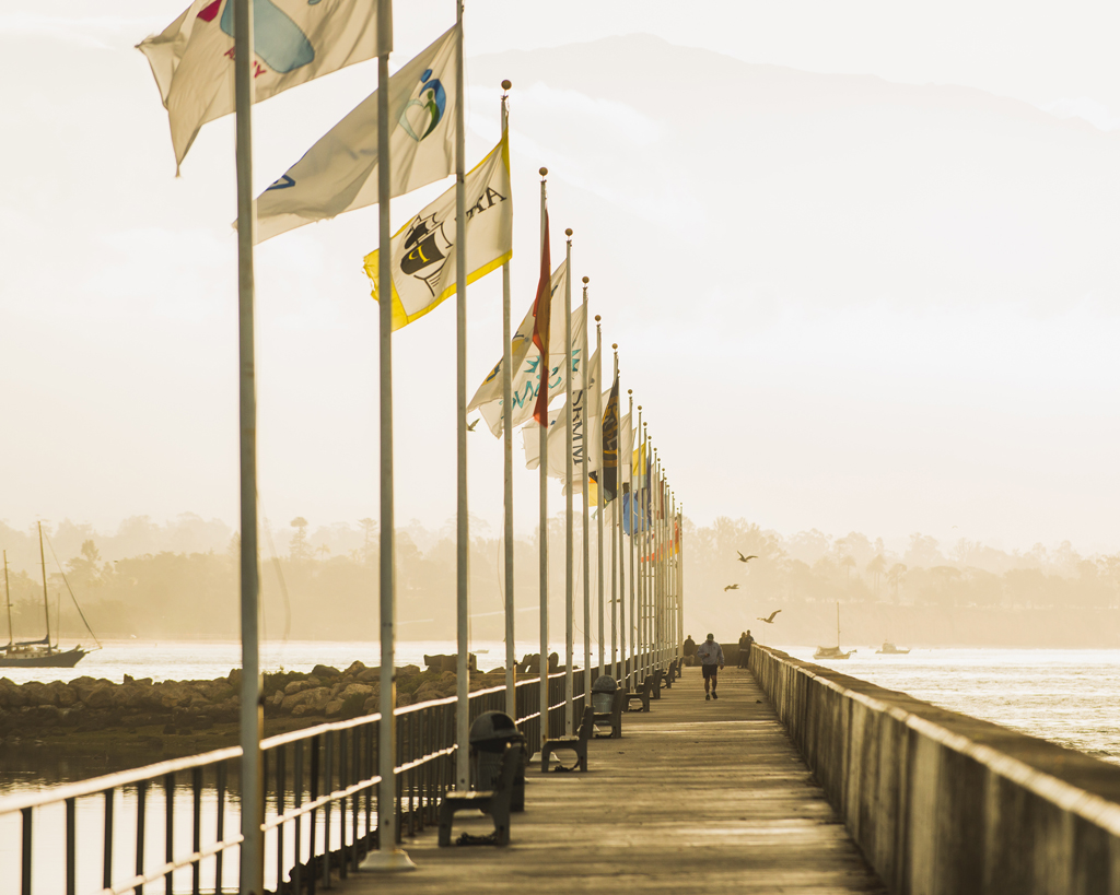 santa barbara breakwater with flag poles along the walkway