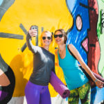 two women dressed in yoga clothes taking a selfie in front of a mural