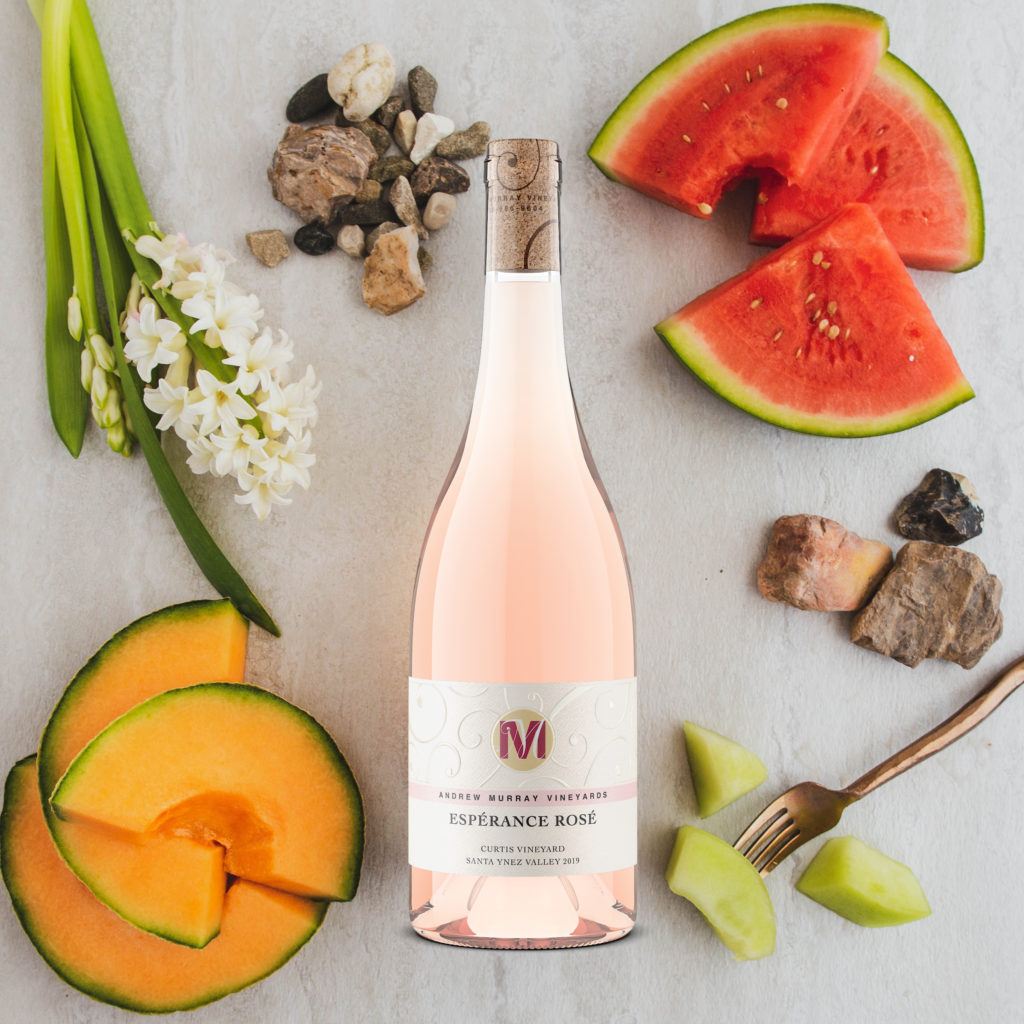 bottle of Andrew Murray Vineyards' Esperance Rose surrounded by fruit, flowers, and rocks