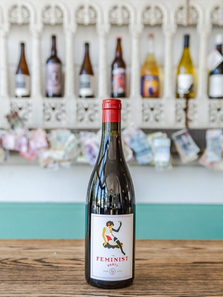 bottle of Casa Dumetz wine sitting on wooden counter in tasting room with bottles of wine on a shelf in the background