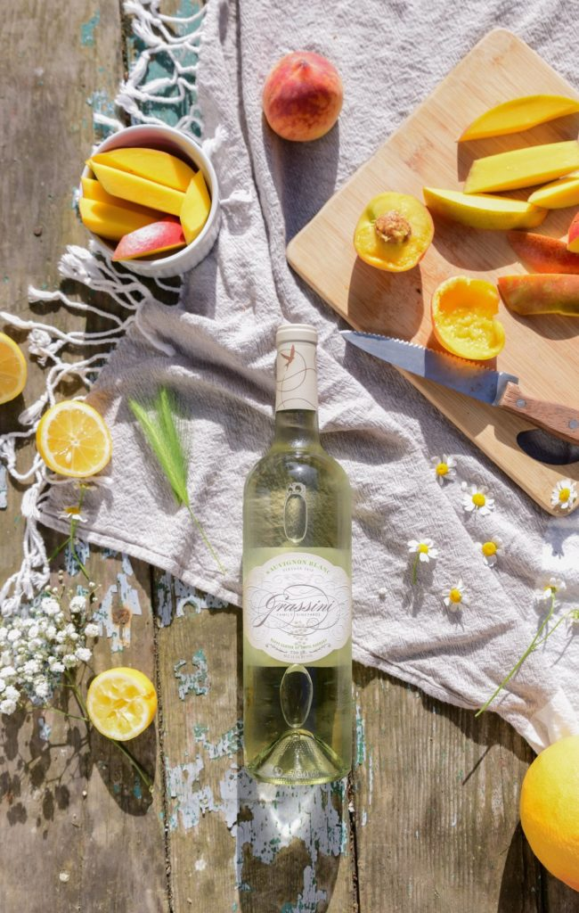 bottle of Grassini Family Vineyard's sauvignon blanc laying on a picnic table with fruit and flowers