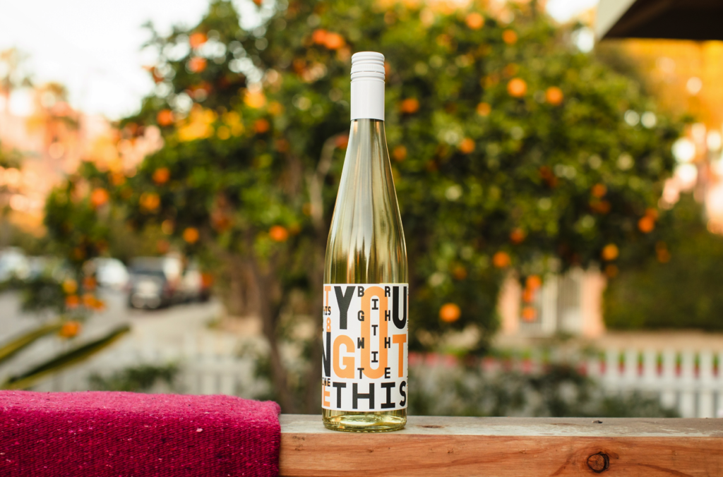 bottle of white wine from Municipal Winemakers on a wooden table outside with an orange tree in the background