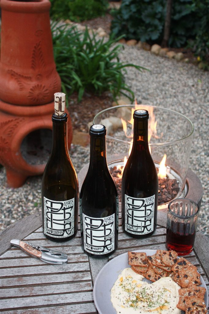 3 bottles of Potek Winery Wine sitting on a wooden table outside with a clay fireplace in the background