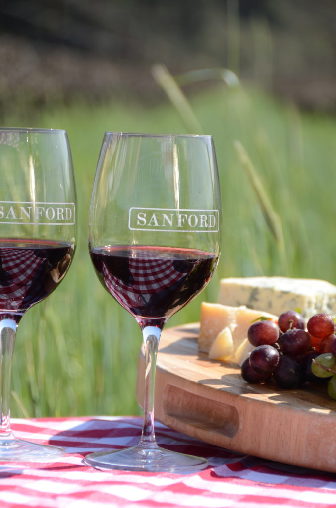 two glasses of red wine from Sanford Winery set on a red and white checkered tablecloth next to a cheeseboard