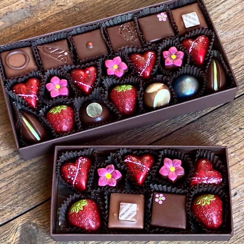 two boxes of chocolates shaped like flowers, hearts, and strawberries from chocolate maya