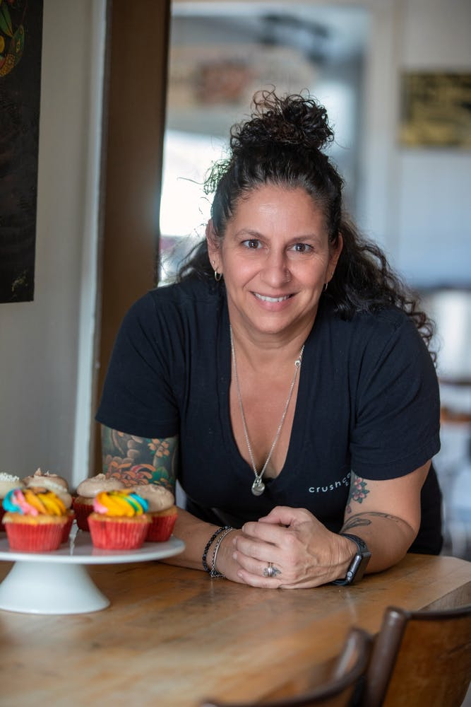 owner of crushcakes cafe standing behind counter with a cake stand holding cupcakes