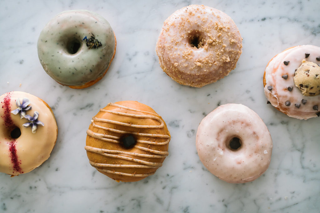 six gourmet donuts from hook & press arranged on a marble surface