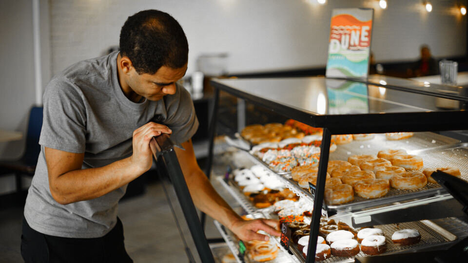 Onus donuts employee reaching into display case full of donuts