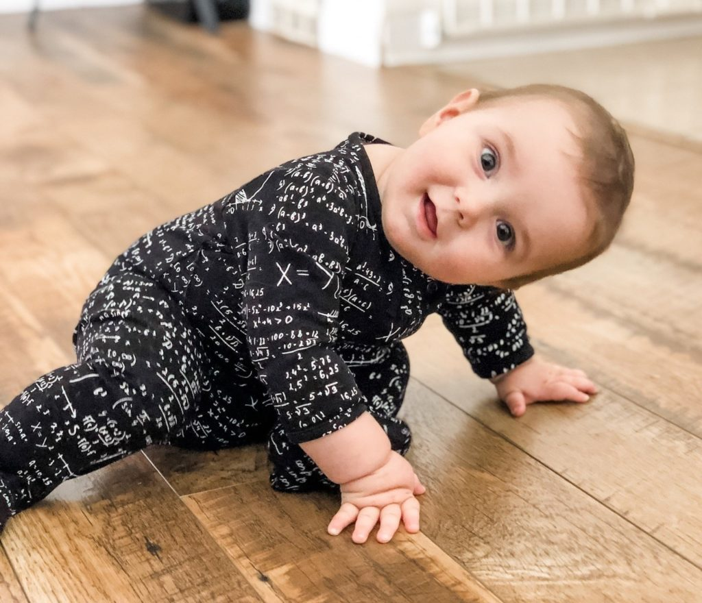 baby crawling on wood floors looking up at camera and wearing a math print onesie from Asher Market