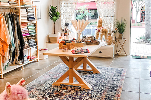 inside of Asher Market store, patterned rug in center of floor with a wooden display table, clothes hanging on both sidewalls