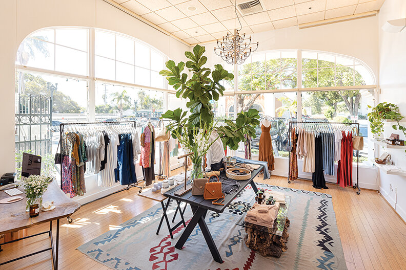 interior of Chapala & Parker boutique with two large windows with clothing racks and a colorful rug with a display table in the center