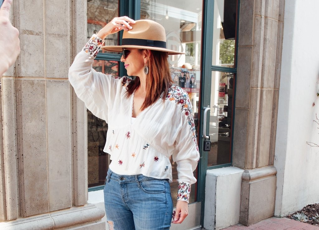 owner Elvia Sanchez standing outside the Evangelina Boutique wearing a straw hat, white floral blouse, and jeans